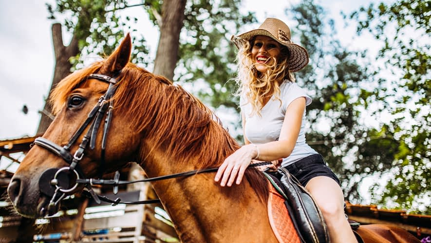 Lachende Frau auf einem Pferd
