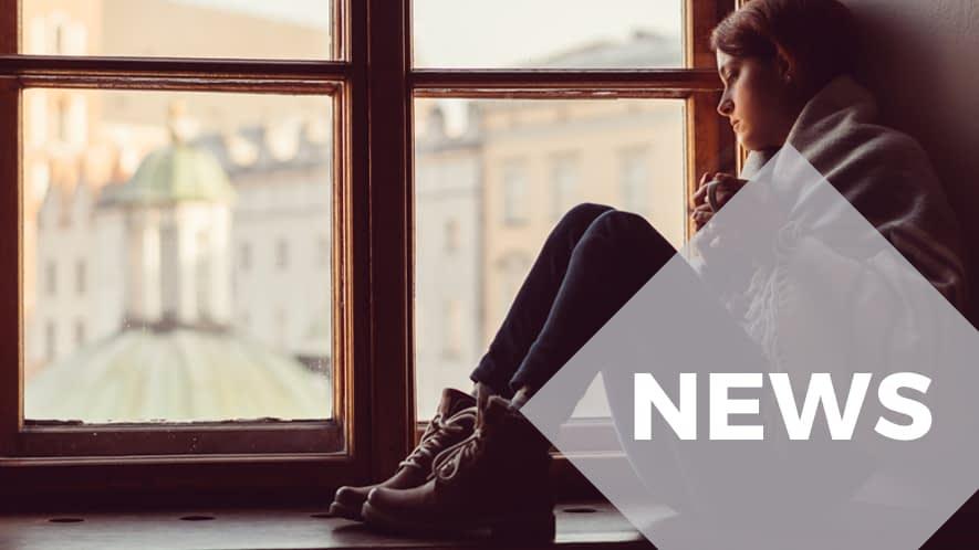 Junge Frau sitzt mit Teetasse auf Fensterbank