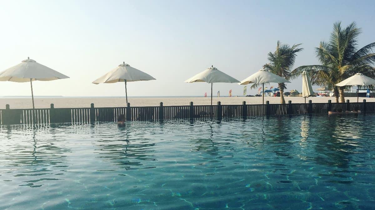 Sonnenschirme, Palmen und Wasser