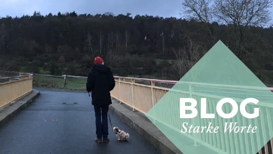 Starke Worte: Mann mit Hund auf einer Brücke an einem grauen Herbsttag