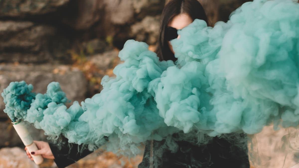 Frau hinter farbiger Rauchwolke