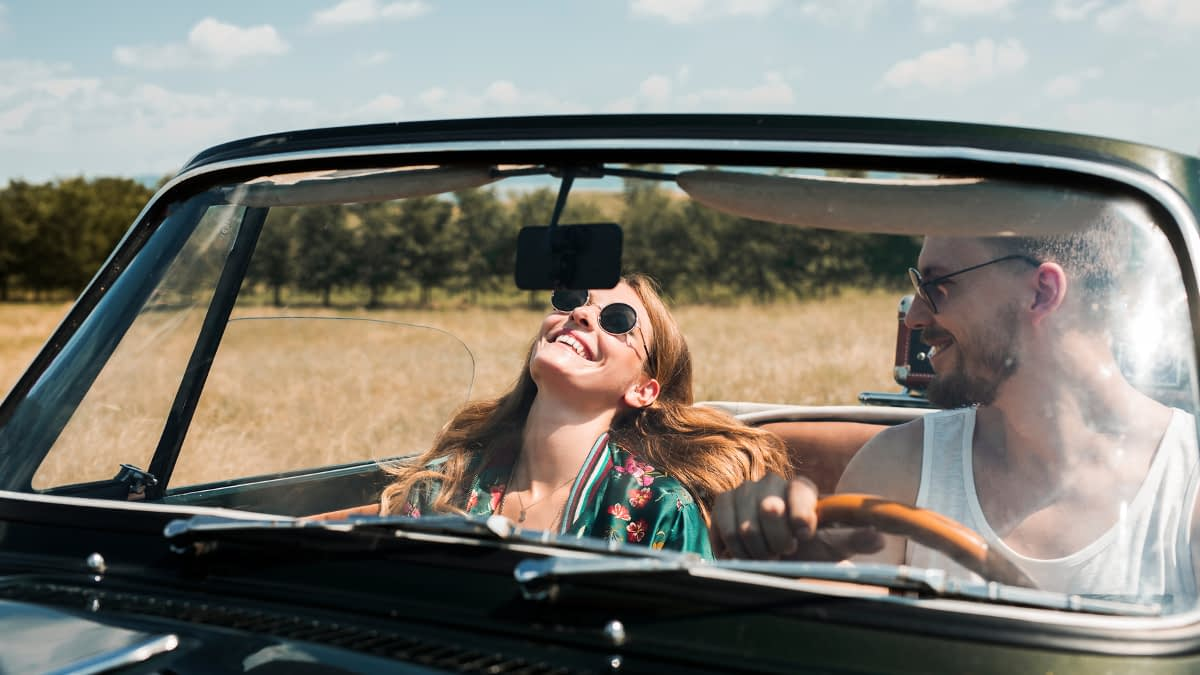 Zwei junge Menschen lachend im Auto