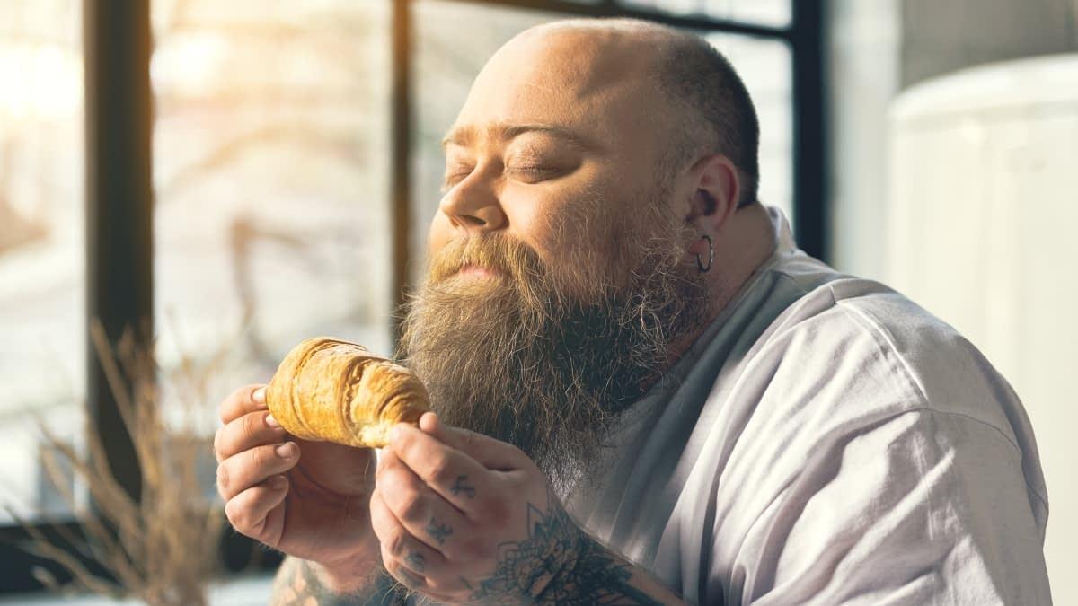 Mann riecht an Croissant