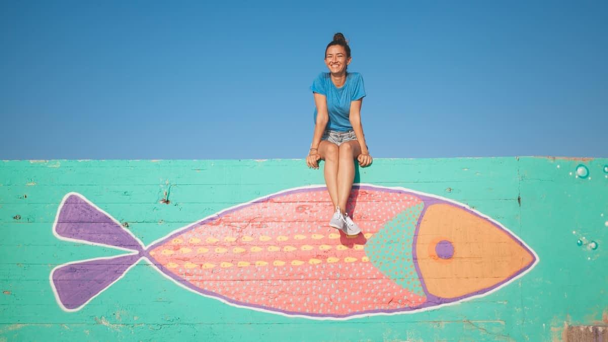 Mädchen sitzt auf einer Mauer mit Fisch-Graffiti