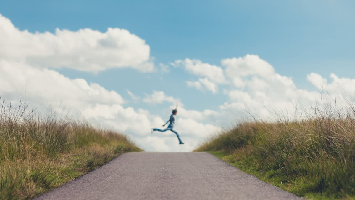 Teenager springt über einen Weg in den Dünen
