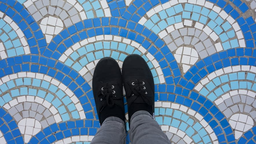 Füße auf buntem Mosaiksteinboden