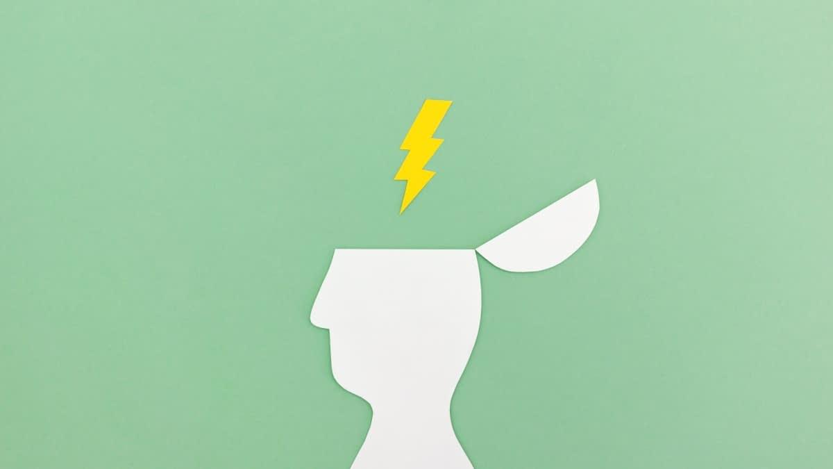 Weißer Kopf im Profil aus Papier mit Blitz