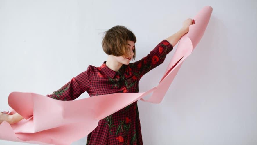Frau zerreißt rosa Papier