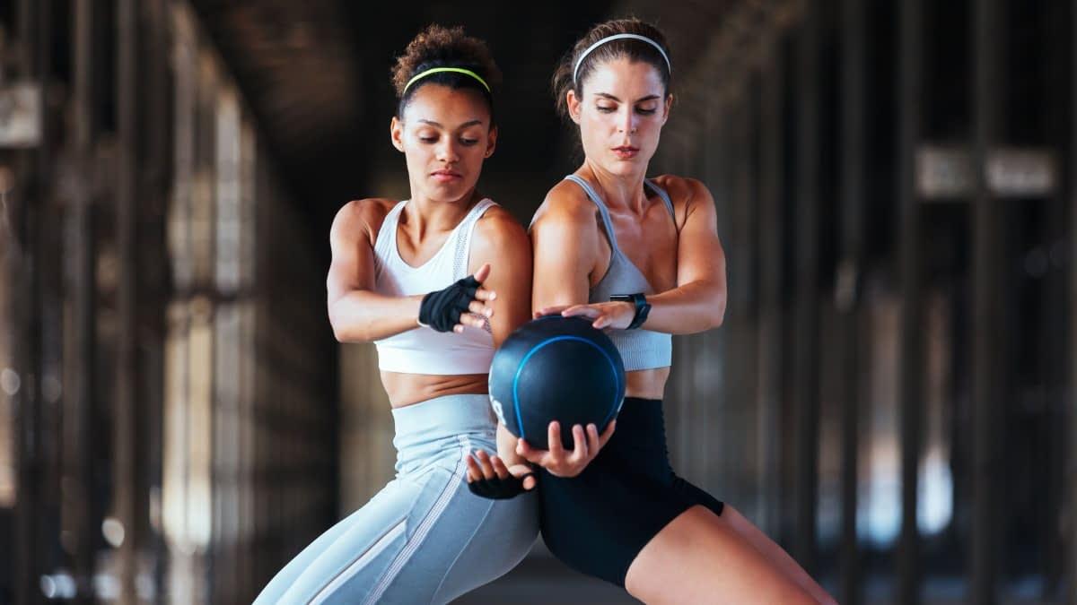 Zwei Frauen stehen Rücken an Rücken und reichen sich einen Ball