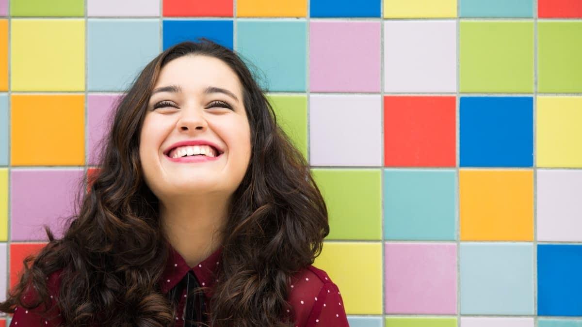 Lachende Frau vor bunter Wand