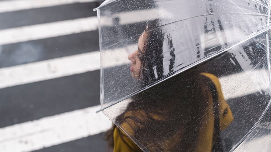 Junge Frau unter einem Regenschirm.