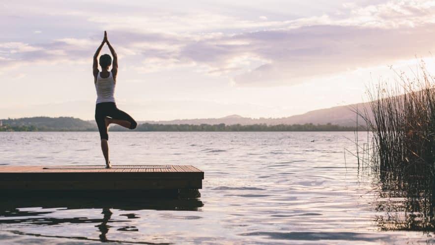 Yoga Übung der Baum auf einem Steg am Wasser
