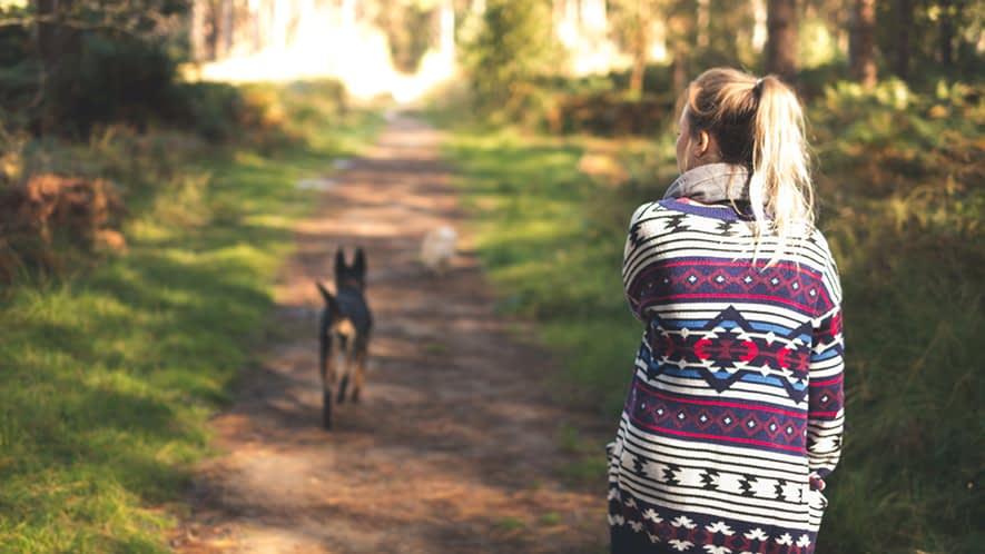 Frau geht mit ihrem Hund spazieren