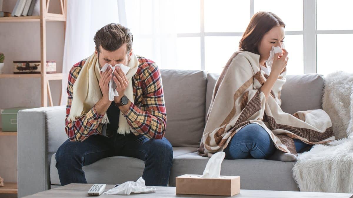 Krankes Pärchen auf einem Sofa die Nase putzend