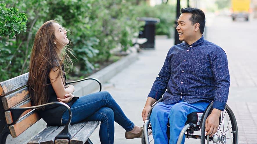 Frau auf einer Bank und Mann im Rollstuhl unterhalten sich