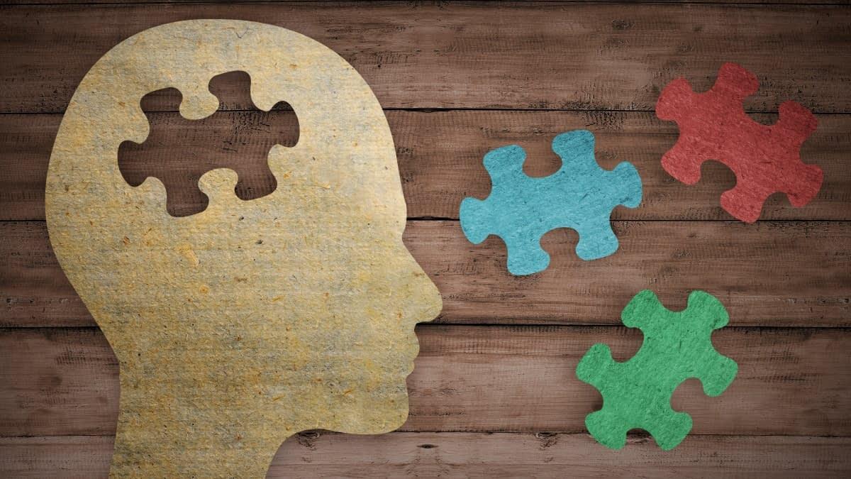 Kopfprofil aus Papier auf Holzuntergrund mit Puzzleteilen
