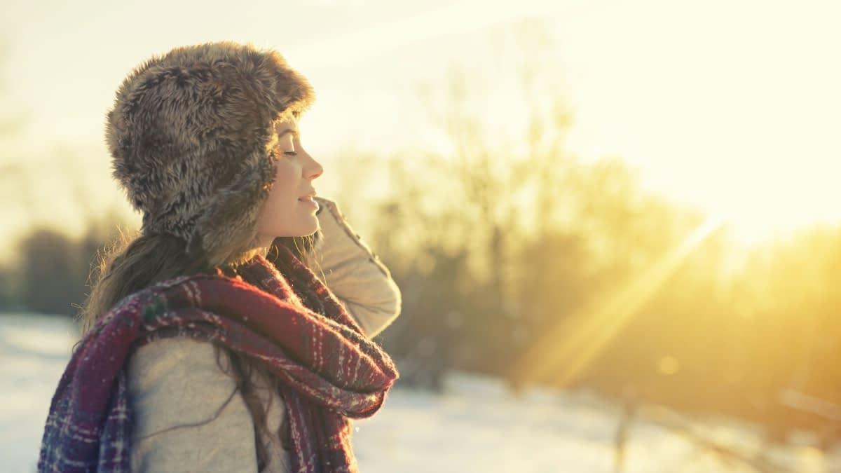 Frau vor Winterlandschaft mit Sonne