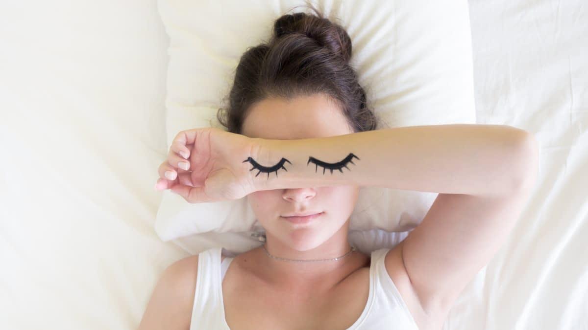 Frau mit Unterarm vor dem Gesicht, auf dem geschlossene Augen aufgemalt sind