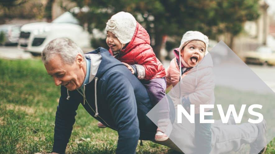 Älterer Herr macht Liegestütz mit Enkelkindern auf dem Rücken