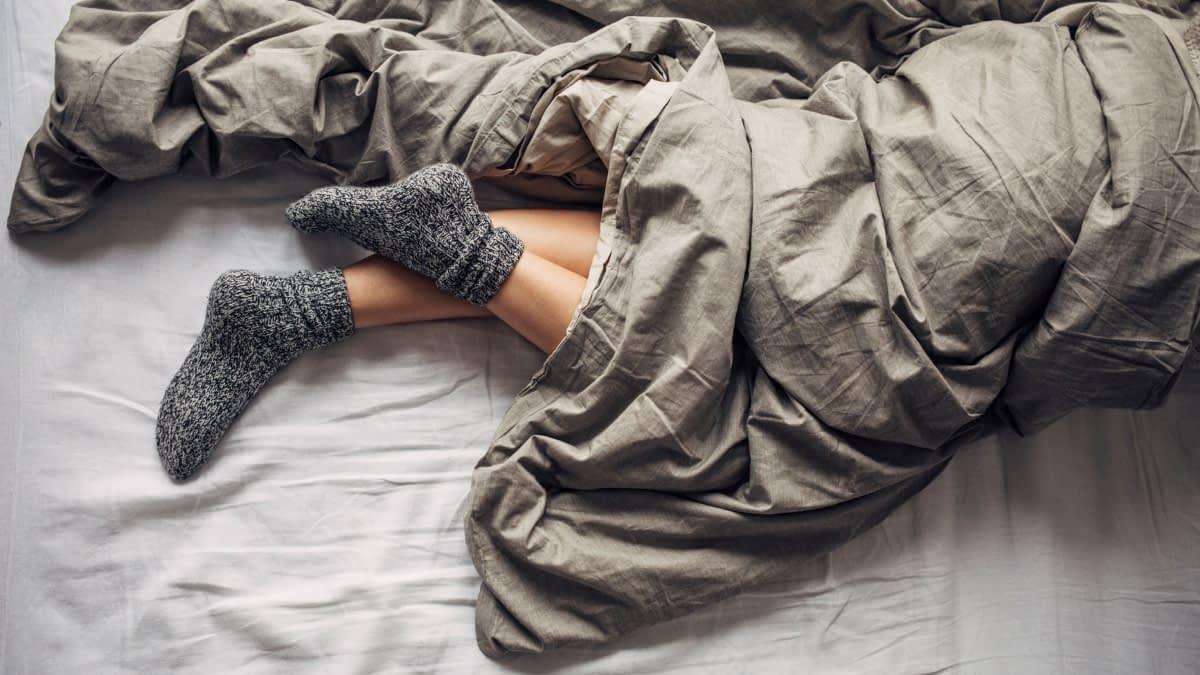 Füße mit Socken gucken unter Bettdecke hervor