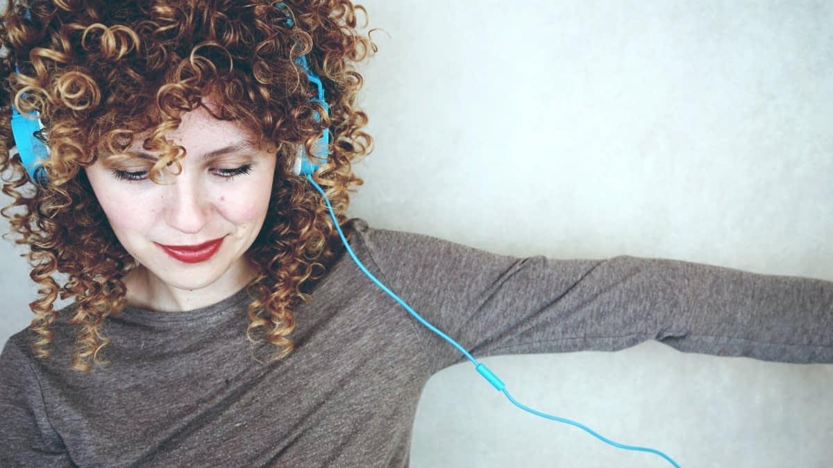 Lächelnde Frau mit Locken und blauem Kopfhörer
