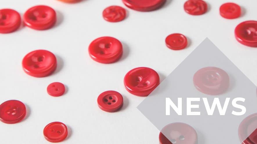 Kleine und große rote Knöpfe wahllos verteilt auf grauem Untergrund