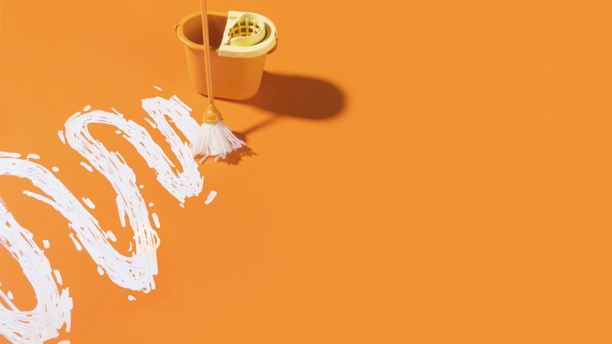 Eimer und Wischmob mit weißer geschlängelter Farblinie auf orangefarbenem Untergrund