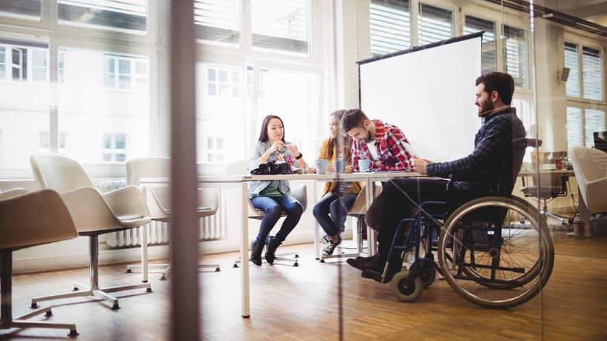 Mann im Rollstuhl im Gespräch mit Arbeitskollegen