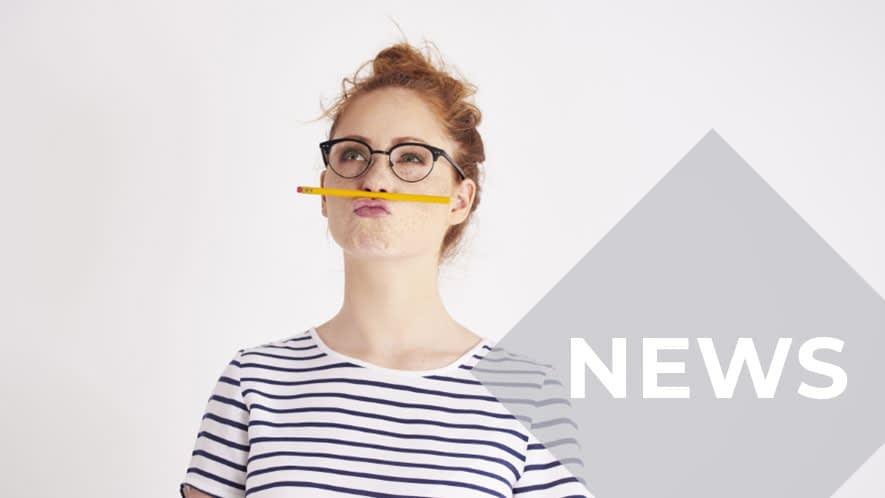Frau mit Brille und gestreiftem Shirt balanciert Bleistift auf Oberlippe