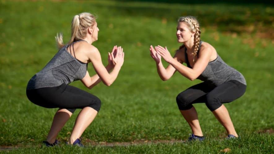 Zwei Frauen machen Kniebeugen