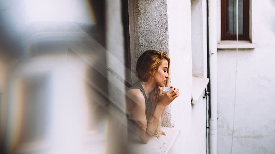 Frau, die aus dem Fenster sieht und Tee trinkt