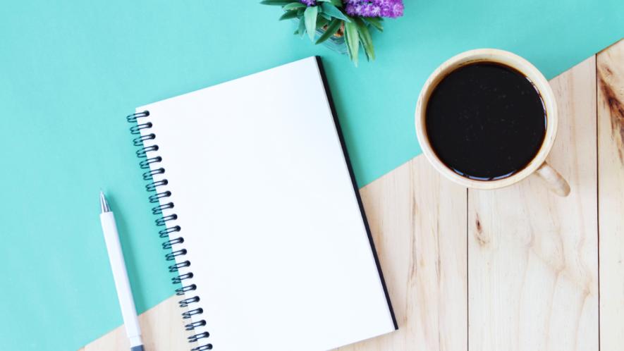 Schreibblock, Stift und eine Tasse Kaffee