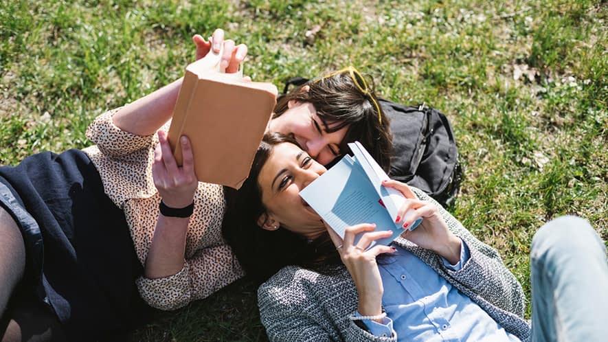 Zwei Freundinnen liegen auf der Wiese und lesen