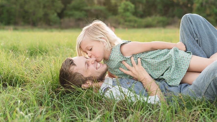 Kind liegt mit Vater auf einer Wiese