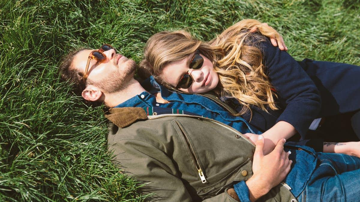 Ein Paar liegt kuschelnd auf einer Wiese