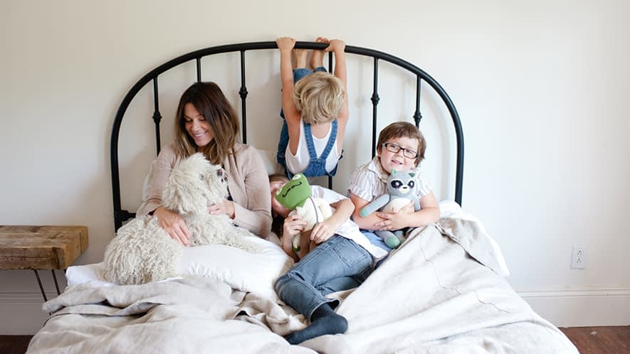 Mutter mit drei Kindern und Hund im Bett