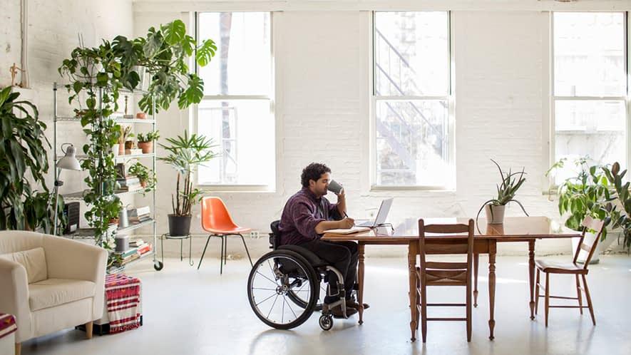 Mann im Rollstuhl sitzt am Tisch und trinkt Tee