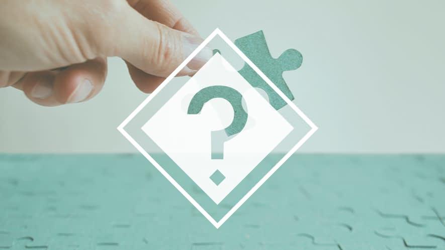 Fragezeichen vor Hand, die Puzzlestück hält