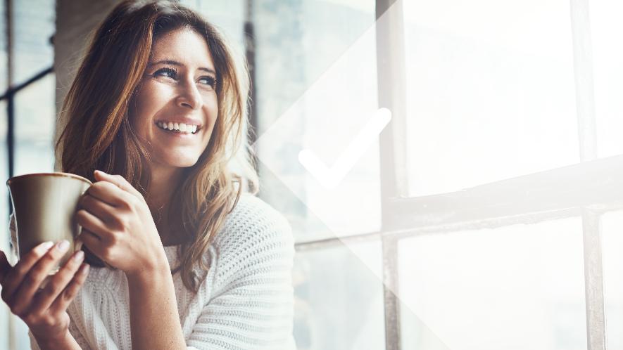 Frau sitzt mit einer Tasse am Fenster und lächelt