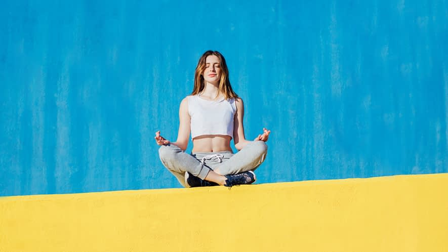 Frau macht Yoga auf einer Mauer