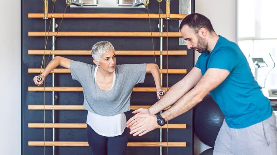 Ältere Frau macht Übungen in einem Fitness-Studio