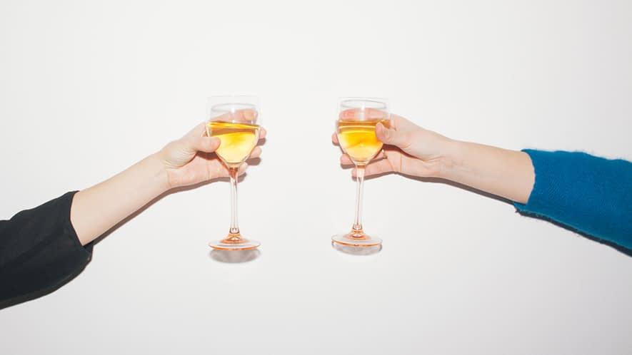 Zwei Personen prosten sich mit einem Glas Sekt zu