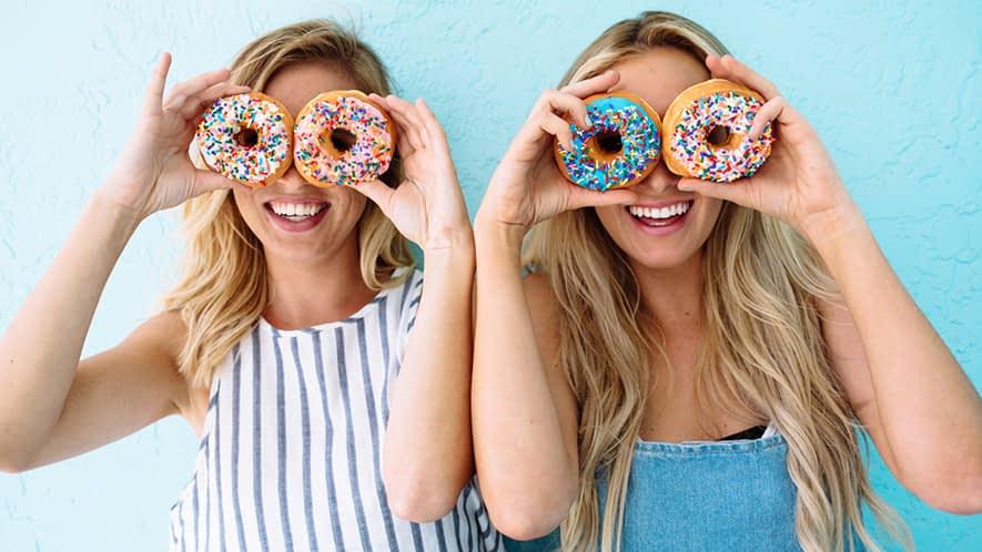 Zwei Frauen albern mit Donuts herum