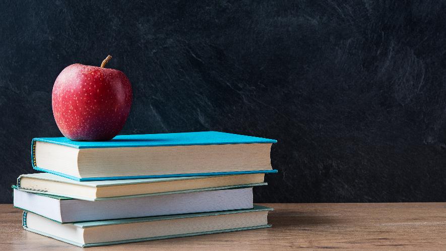 Apfel, der auf gestapelten Büchern liegt