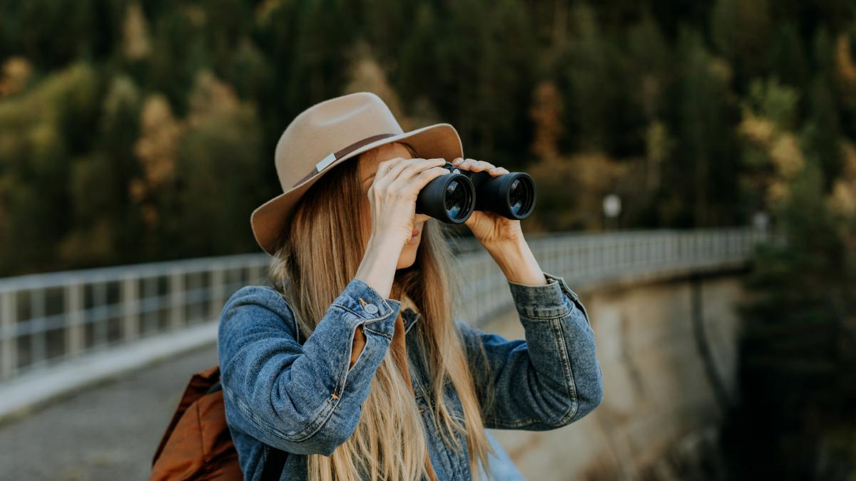 Frau steht auf einer Brücke und schaut durch ein Fernglas