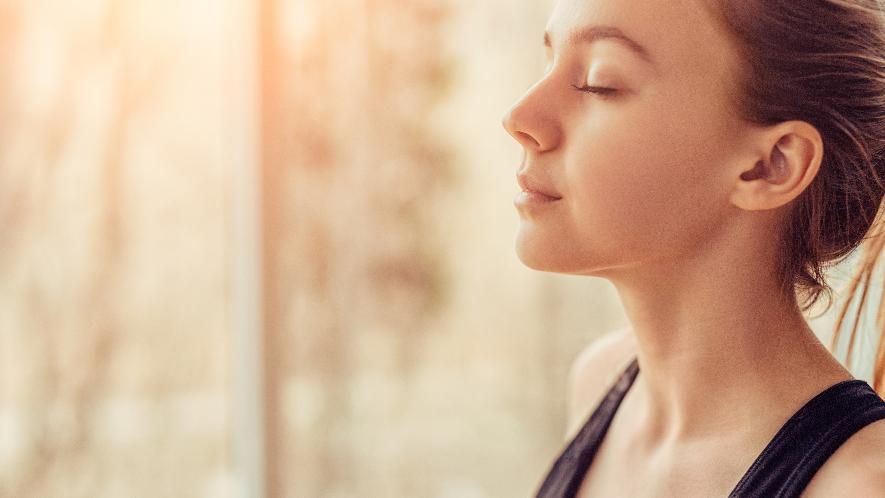 Junge Frau mit geschlossenen Augen atmet durch