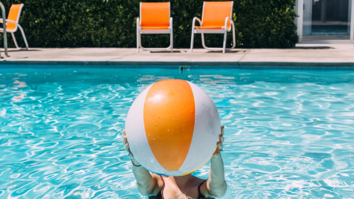 Frau im Pool hält einen Gummiball vor ihr Gesicht