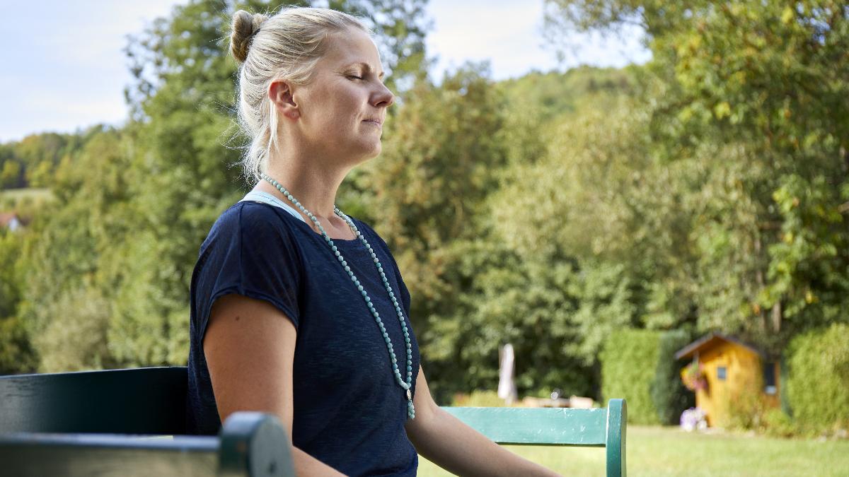 MS-Betroffene Andrea sitzt mit geschlossenen Augen auf einer Parkbank