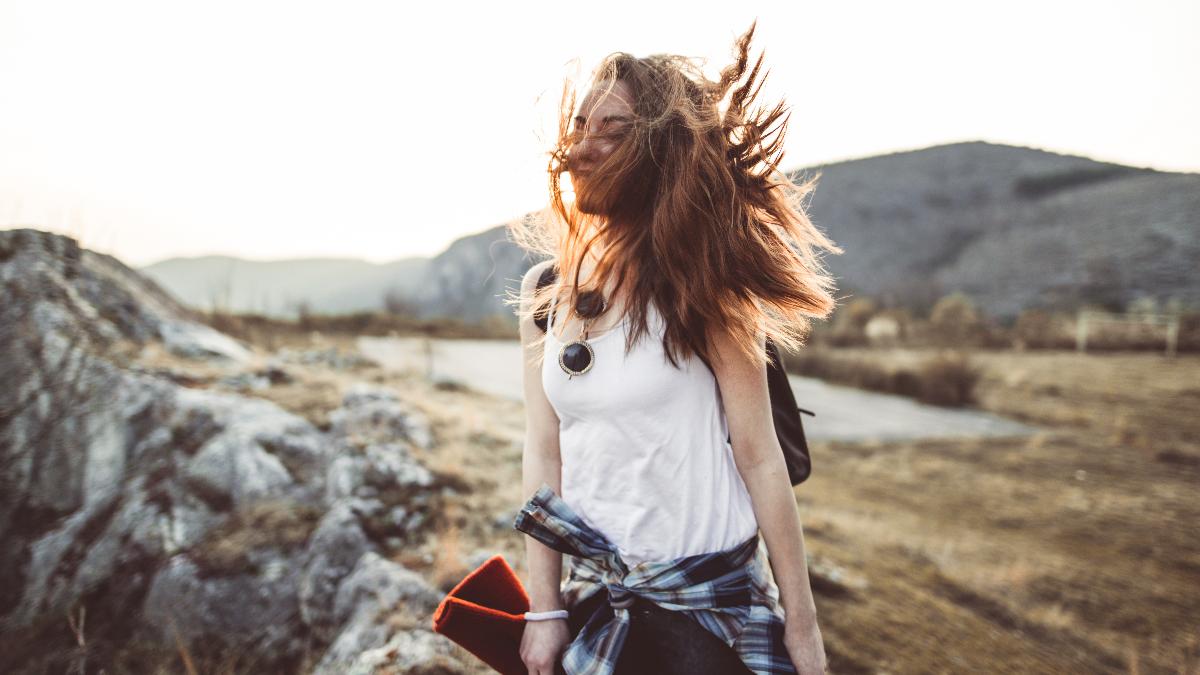Frau ist vor einem Berg zu sehen, der Wind verweht ihr Haar.