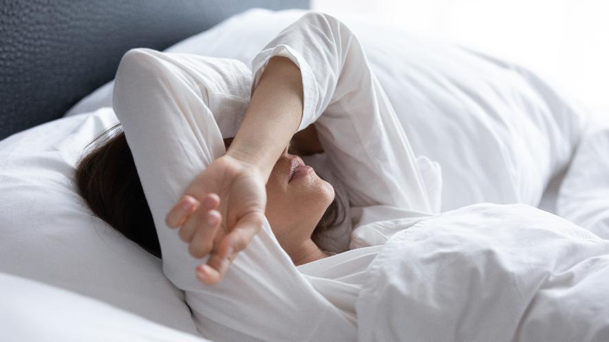 Frau liegt im Bett, Arme über dem Kopf verschränkt